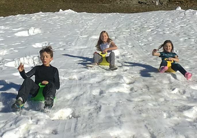 """Mercredi, à 13 heures, à la station de Sainte-Foy, Evan, Mari-Lou et Salomé, profitent de leur après-midi de libre pour glisser en luge, sur le tas de neige en formation, créé par le """"canon à neige"""". Premières glisses pour ses enfants locaux. Un avant-goût des plaisirs d'hiver, qu'ils sont impatients de renouveler à chaque occasion."""